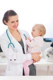 Gelukkige pediater arts met baby op onderzoek royalty-vrije stock afbeelding