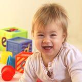 Gelukkige peuter met helder speelgoed Stock Afbeeldingen