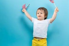 Gelukkige peuterjongen die Amerikaanse vlaggen golven Stock Foto's
