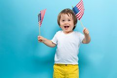 Gelukkige peuterjongen die Amerikaanse vlaggen golven stock fotografie