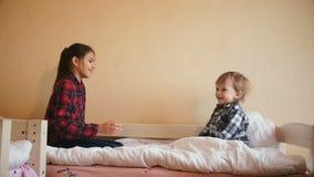 Gelukkige peuterjongen die met tienerzuster op matras bij slaapkamer springen stock video