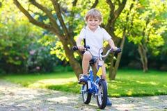 Gelukkige peuterjongen die zijn eerste fiets berijden Stock Foto's