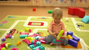 Gelukkige peuterkinderen die met multi gekleurde blokken bij binnenspeelplaats spelen De activiteit van de kindsport stock videobeelden
