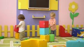 Gelukkige peuterkinderen die met zachte multi gekleurde blokken bij binnenspeelplaats spelen De activiteit van de kindsport stock video