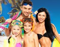 Gelukkige pretfamilie met twee kinderen bij tropisch strand Stock Foto's