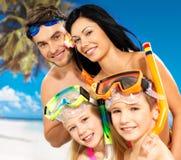 Gelukkige pretfamilie met twee kinderen bij tropisch strand Stock Afbeeldingen
