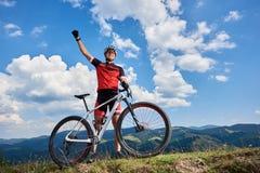 Gelukkige professionele sportmanfietser die zich met de dwarsfiets van het land op een heuvel bevinden, rasing hand royalty-vrije stock foto's