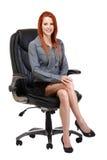 Gelukkige redhead vrouwenzitting op stoel stock foto