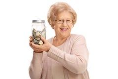 Gelukkige rijpe dame die een kruik houden die met geld wordt gevuld stock foto