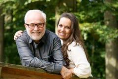 Gelukkige rijpe man die met jonge vrouw glimlachen stock foto's