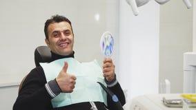 Gelukkige rijpe mens die duimen na tandonderzoek tonen stock videobeelden