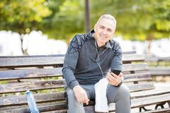 Gelukkige rijpe mens die een onderbreking van het uitoefenen in een park nemen Stock Fotografie
