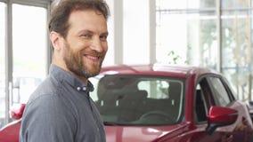 Gelukkige rijpe mens die tonend zijn autosleutels bij de het handel drijventoonzaal glimlachen stock footage