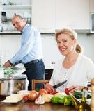 Gelukkige rijpe paar kokende groenten Royalty-vrije Stock Foto's