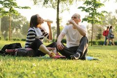 Gelukkige rijpe paarzitting in het park op fitness mat, rustende het drinken yoghurt na sportenoefeningen royalty-vrije stock fotografie