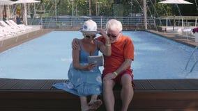 Gelukkige rijpe paarzitting op de rand van de pool met tablet in handen Het leuke hogere man en vrouwen ontspannen in stock footage