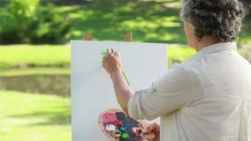 Gelukkige rijpe vrouw die op een canvas trekken stock footage