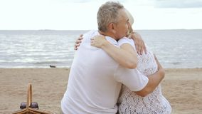 Gelukkige rijpe vrouw en teruggetrokken man die op kust koesteren stock videobeelden