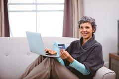 Gelukkige rijpe vrouw met creditcard die laptop met behulp van stock foto