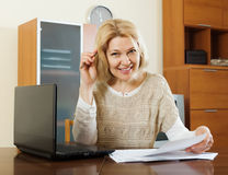 Gelukkige rijpe vrouw met laptop en documenten Stock Foto