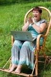 Gelukkige rijpe vrouw met laptop in schommelstoel Stock Afbeeldingen