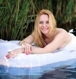 Gelukkige romantische vrouwenvreugde die in meer blauw water rusten Stock Afbeelding