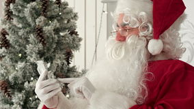 Gelukkige Santa Claus die Kerstmis e-mail van jonge geitjes controleren op zijn telefoon stock video