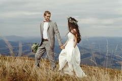 Gelukkige schitterende bruid en bruidegom die in zon lichte holding han lopen stock foto