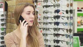 Gelukkige schitterende jonge vrouw die op de telefoon spreken terwijl eyewear winkelen stock videobeelden