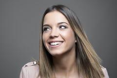 Gelukkige schitterende jonge vrouw die weg met witte toothy glimlach kijken Royalty-vrije Stock Afbeelding