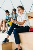 gelukkige schooljongen die in notitieboekje schrijven en camera bekijken terwijl zijn klasgenoten stock foto