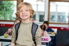 Gelukkige Schooljongen met Klasgenoten die binnen bestuderen stock foto's