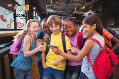 Gelukkige schoolkinderen die slimme telefoon met sociale media pictogrammen met behulp van royalty-vrije stock afbeeldingen