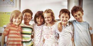 Gelukkige schoolkinderen die zich in klaslokaal bevinden stock afbeeldingen