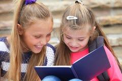 Gelukkige schoolmeisjes die een boek lezen Royalty-vrije Stock Afbeeldingen