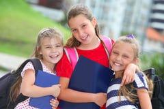 Gelukkige schoolmeisjes met rugzakken stock foto