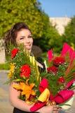 Gelukkige schoonheid met bloemboeketten royalty-vrije stock afbeeldingen