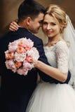 Gelukkige sensuele knappe bruidegom en blonde mooie bruid in wit Royalty-vrije Stock Foto's