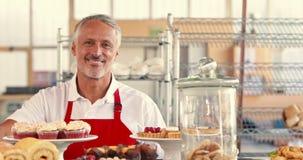 Gelukkige server die camera met duimen omhoog achter cakes bekijken stock footage