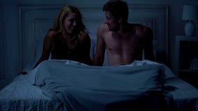 Gelukkige sexy echtgenoot en vrouw die pret in bed hebben onder algemene, prettige ogenblikken stock foto's