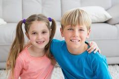 Gelukkige siblings die bij camera samen glimlachen Stock Afbeeldingen