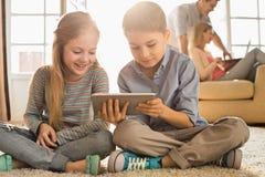 Gelukkige siblings die digitale tablet op vloer met ouders op achtergrond gebruiken Stock Foto's