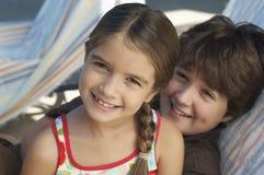 Gelukkige Siblings die op Deckchair ontspannen stock afbeelding