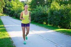 Gelukkige slanke joggingvrouw die in park lopen Stock Foto's