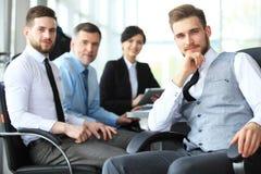 Gelukkige slimme bedrijfsmens die met teampartners op de achtergrond bespreken royalty-vrije stock fotografie