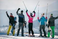 Gelukkige snowboarders genieten van het sneeuwwitte landschap van bergen en Stock Afbeeldingen