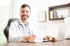 Gelukkige Spaanse arts die in een bureau werken Stock Foto