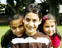 Gelukkige Spaanse siblings samen voor boom royalty-vrije stock afbeelding