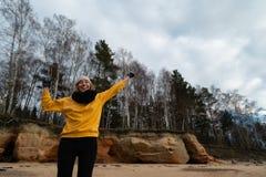 Gelukkige sport en manierminnaarenthousiast die op een strand uitwerken die heldere gele sweater en zwarte handschoenen en een GL stock foto