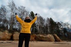 Gelukkige sport en manierminnaarenthousiast die op een strand uitwerken die heldere gele sweater en zwarte handschoenen en een GL stock afbeeldingen